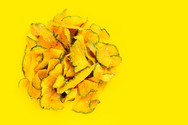 Chip di fetta di zucca verde su sfondo giallo.