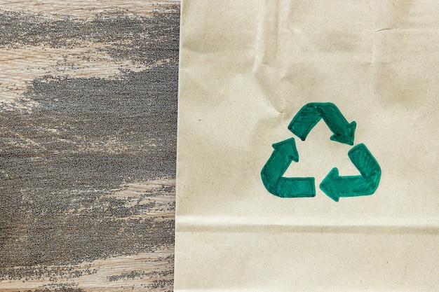 Simbolo di riciclo verde su sfondo di cartone di carta, concetto ecologico e di sostenibilità