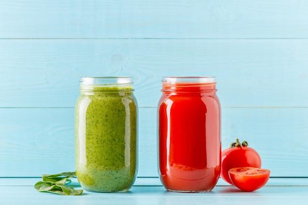 Frullati / succhi di colore verde / rosso in un barattolo