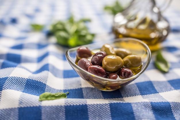 Olive verdi e rosse in una ciotola con olio d'oliva e caraffa in background.