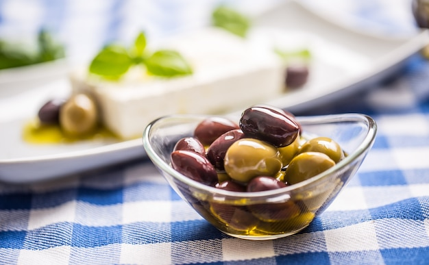 Olive verdi e rosse in una ciotola con olio d'oliva e formaggio feta greco in background.
