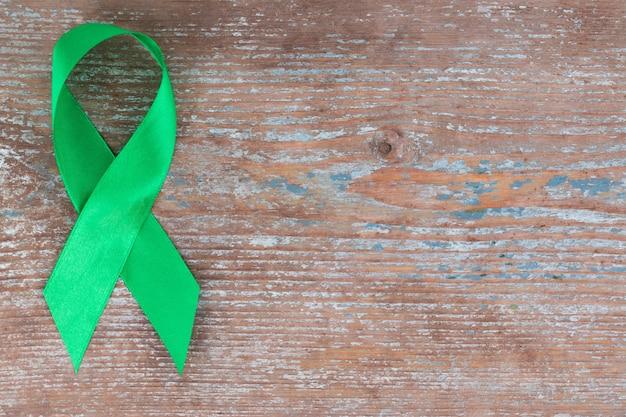 Nastro verde. scoliosi, salute mentale e altro, simbolo di consapevolezza sullo sfondo di legno