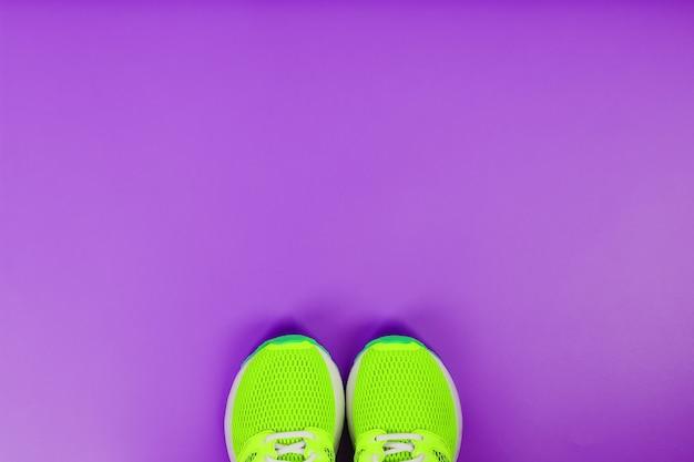 Scarpe da corsa verdi su sfondo viola. vista dall'alto, spazio libero