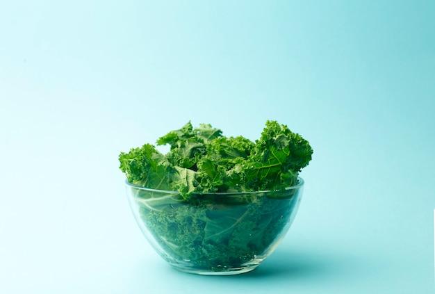 Insalata verde in una ciotola di vetro sul blu