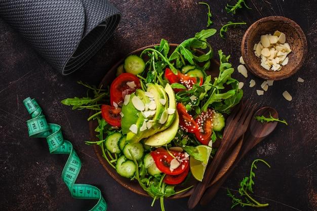 Insalata verde con avocado, pomodori, cetrioli e noci in un piatto di legno