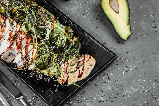 Insalata verde con anguilla affumicata, arance e fette di avocado. disposizione piatta. cucina giapponese.