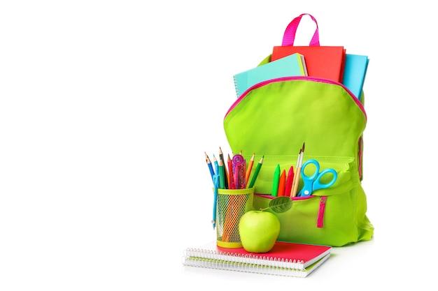 Borsa di scuola verde piena di materiale scolastico isolato su bianco