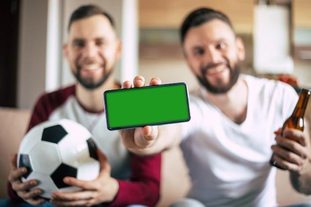 Schermo verde sullo smartphone in mano di entusiasti giovani appassionati di sport barbuti. vincere nelle scommesse