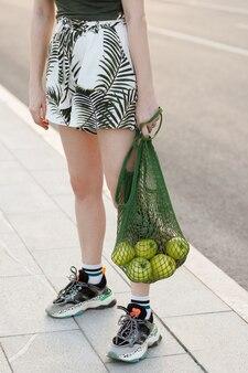 Shopper verde con mele nelle mani della ragazza