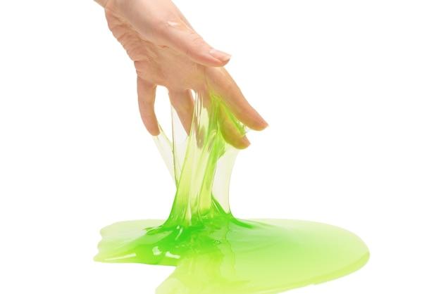 Giocattolo di melma verde in mano di donna isolato su sfondo bianco.