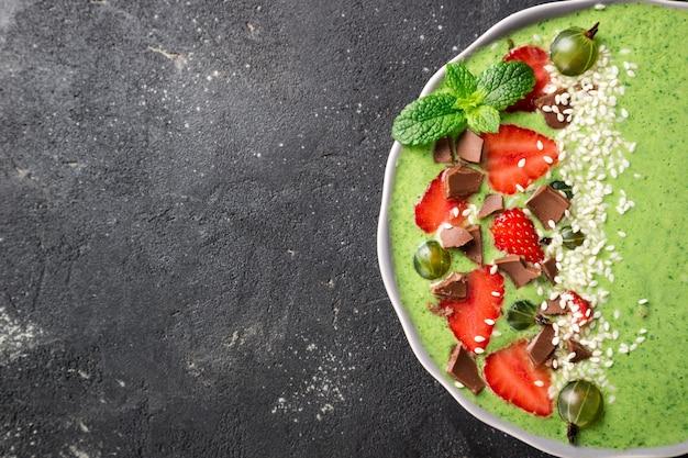 Ciotola di frullato verde con semi di kiwi, spinaci, fragola, uva spina, cioccolato e sesamo