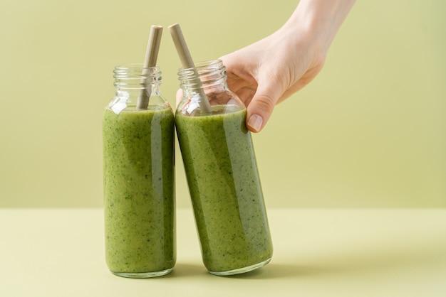 Frullato verde in bottiglie di vetro con tubi di bambù bottiglia della holding della mano della donna