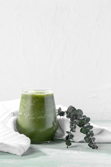 Bicchiere frullato verde con pianta