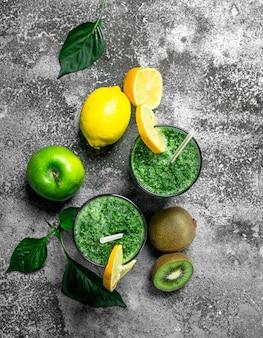 Frullato verde con mela, kiwi ed erbe aromatiche. su fondo rustico.