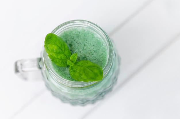 Frullato verde con foglia di menta fresca. vista dall'alto. mangiare sano. spazio per il testo.