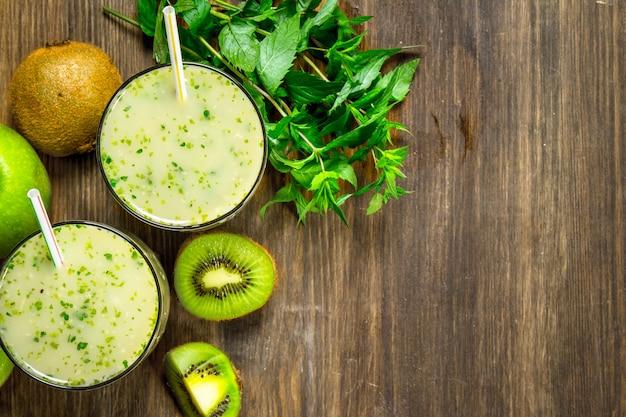 Frullato verde con kiwi e menta sulla tavola di legno.