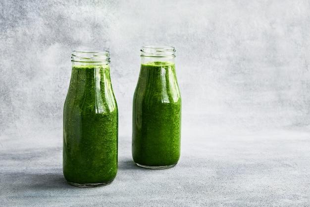 Frullato verde con spinaci in piccole bottiglie su sfondo grigio spazio copia cibo sano concetto