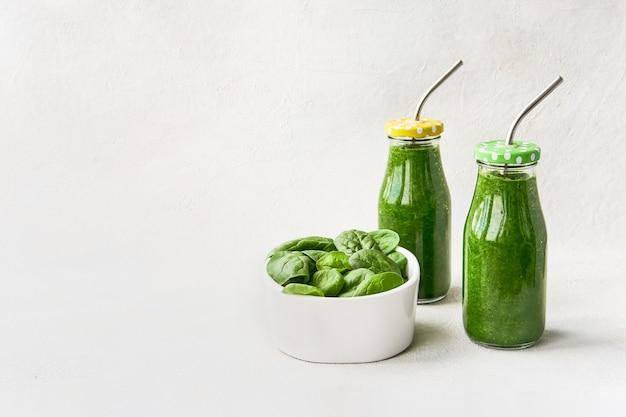 Frullato verde con spinaci in piccole bottiglie e foglie di spinaci in una ciotola su sfondo bianco. copia spazio per il testo. concetto di stile di vita sano