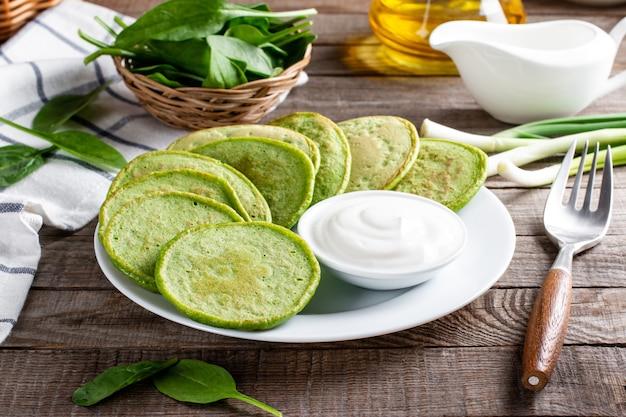 Frittelle di spinaci verdi con panna acida su un tavolo di legno