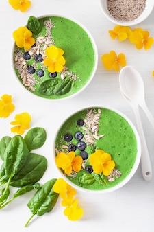 Ciotola di frullato di spinaci verdi con mirtillo, semi di chia e fiori di pansé commestibili