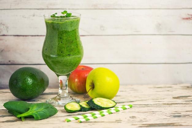 Frullati di spinaci verdi in vetro con ingredienti sul tavolo di legno chiaro.