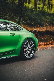 Automobile sportiva verde nella foresta scura