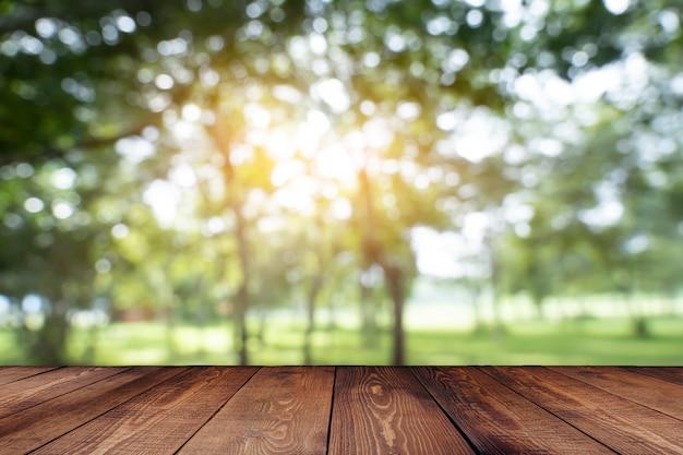 Sfondo verde primaverile con tavolo in legno in estate bella luce arancione