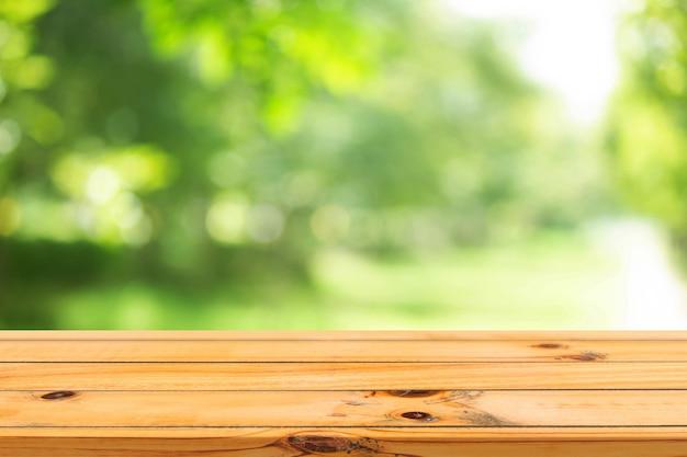 Sfondo verde primaverile con tavolo in legno in estate