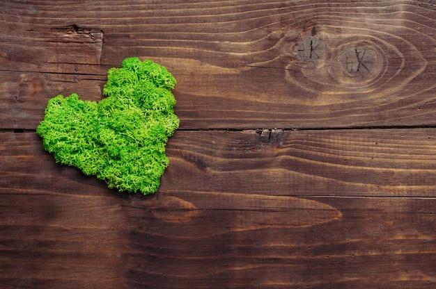 Muschio stabilizzato verde a forma di cuore su fondo di legno rustico scuro con uno spazio vuoto per il testo