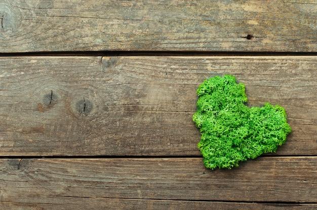 Muschio stabilizzato verde a forma di cuore su fondo di legno rustico con uno spazio vuoto per il testo