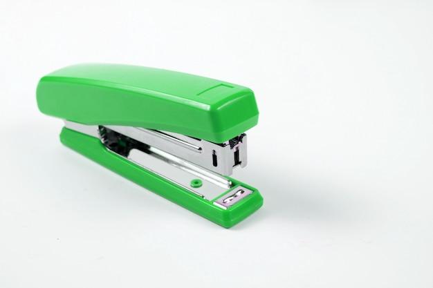 Cucitrice verde con fili di punti metallici su sfondo bianco.
