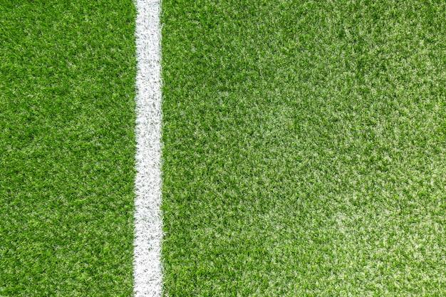 Campo sportivo verde sintetico verde di calcio dell'erba con la linea di banda d'angolo bianca