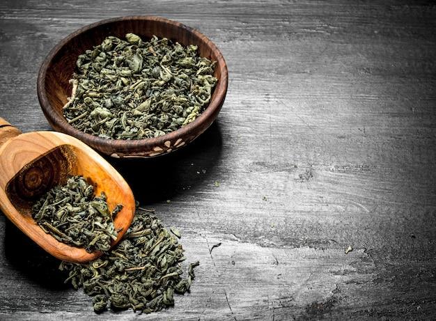 Tè verde in una ciotola con una paletta. sulla lavagna nera