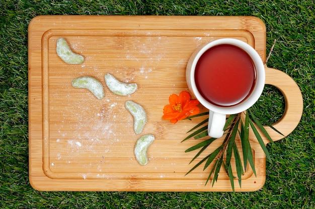 Biscotti del tè verde e tazza di tè sul vassoio di legno