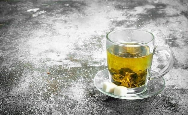 Tè verde in una tazza di vetro su uno sfondo rustico