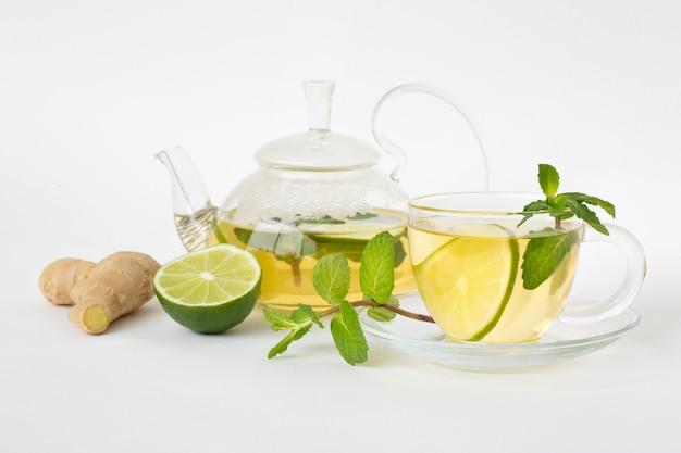 Tè verde in una tazza di vetro e teiera, foglie di menta, lime e zenzero su un tavolo bianco