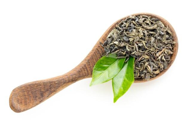 Foglia di tè verde il cucchiaio isolato sulla superficie bianca.