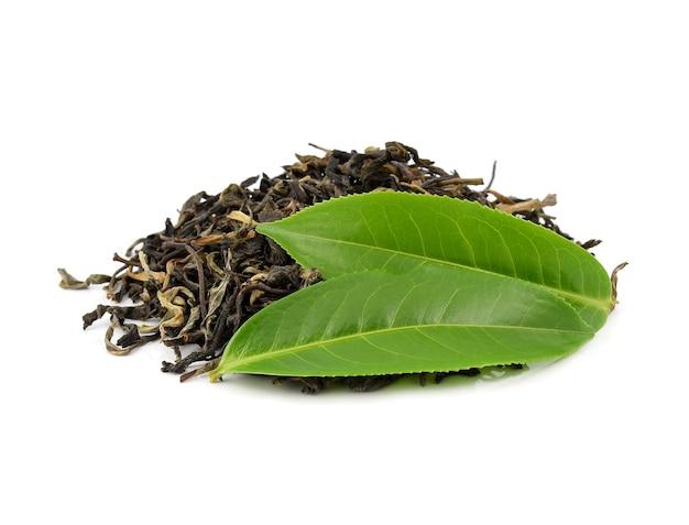 Foglie di tè verde con foglie di tè essiccate isolate su bianco.