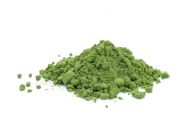 Polvere del tè verde su bianco