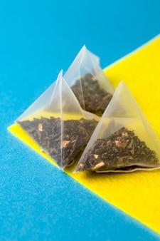 Tè verde in un sacchetto piramidale su sfondo blu e giallo