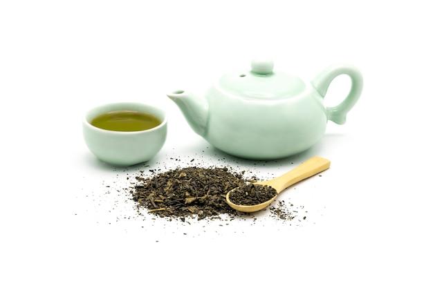 Set da tè verde con foglie verdi secche e cucchiaio di legno isolato su bianco