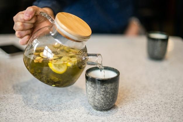 Il tè verde con limone e zenzero da una teiera di vetro viene versato in una tazza