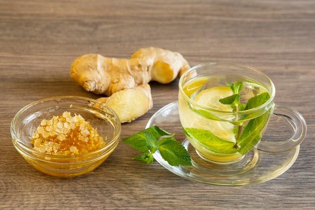 Tè verde con limone e menta, zenzero e miele in una ciotola di vetro su un tavolo di legno
