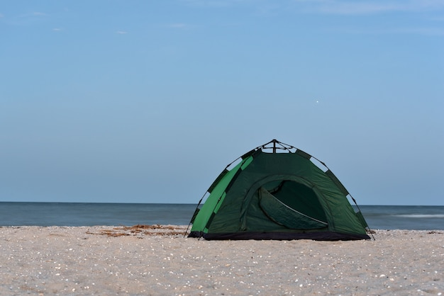 Tenda verde sulla spiaggia di sabbia contro il mare e il cielo blu sullo sfondo. campeggio, turismo attivo.