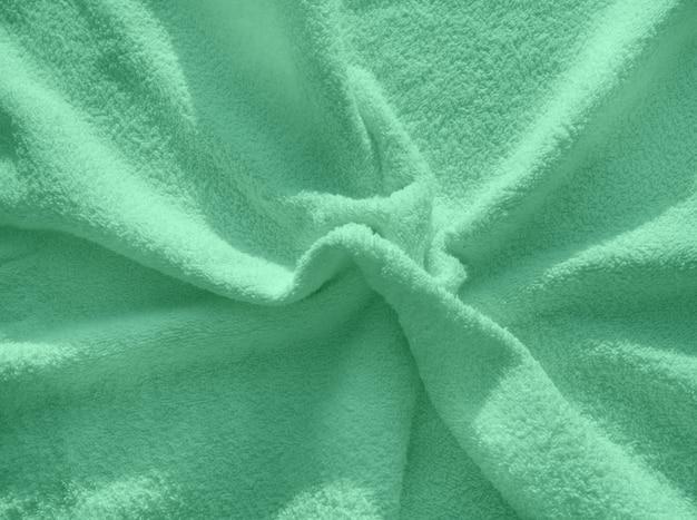 Asciugamano in spugna verde, un semplice esempio della trama di un tessuto morbido e soffice, sfondo