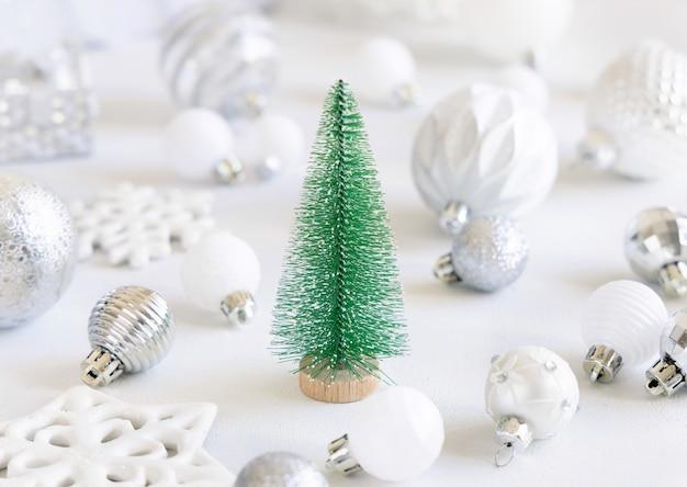 Giocattolo verde abete di natale con decorazioni di natale bianche e argento closeup sul tavolo bianco. composizione invernale monocromatica