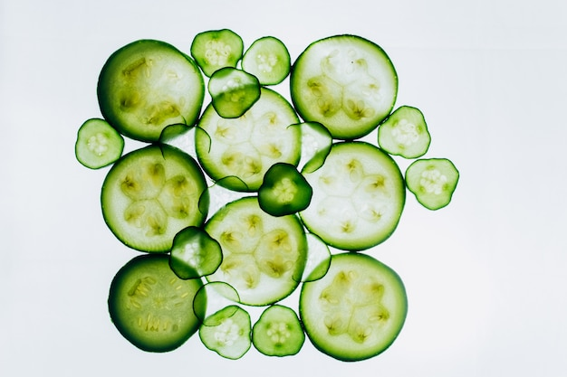 Fette traslucide verdi di cetriolo sui precedenti del primo piano luminoso della luce bianca. dischi trasparenti di verdure. trama di modelli di caleidoscopio in macro