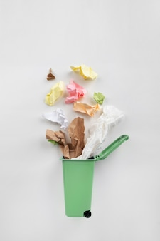 Pattumiera verde con rifiuti di carta su uno sfondo grigio. concetto di riciclaggio