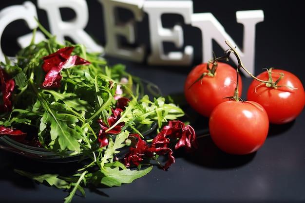 Insalata verde vegana di mix di foglie verdi e verdure. foglie di rucola fresca in uno scolapasta. sfondo nero.