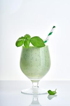 Succo di verdura verde o frullato guarnito con foglie di basilico fresco in bicchiere da cocktail margarita isolato su bianco.